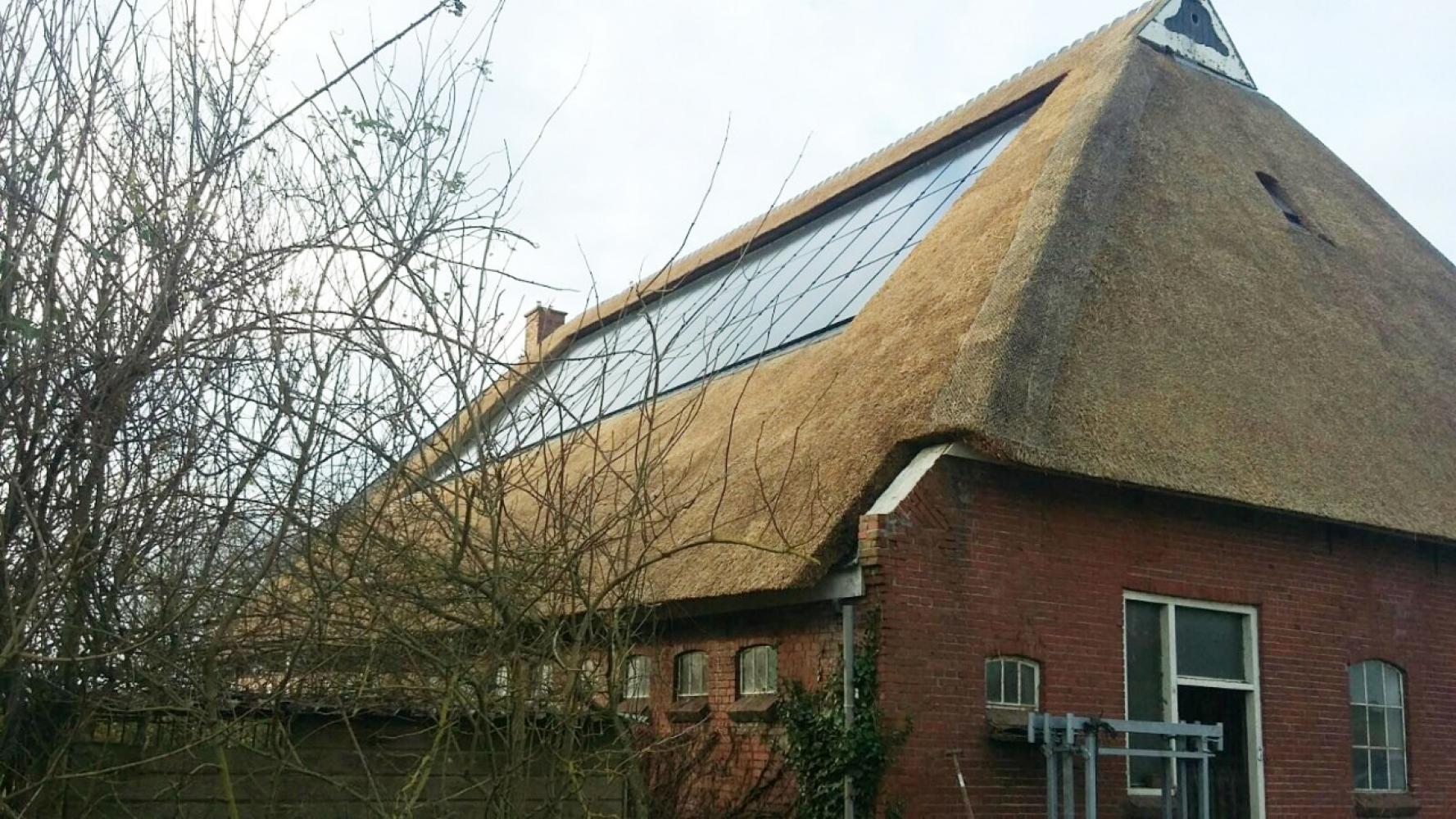 Zonnepanelen op een rieten dak